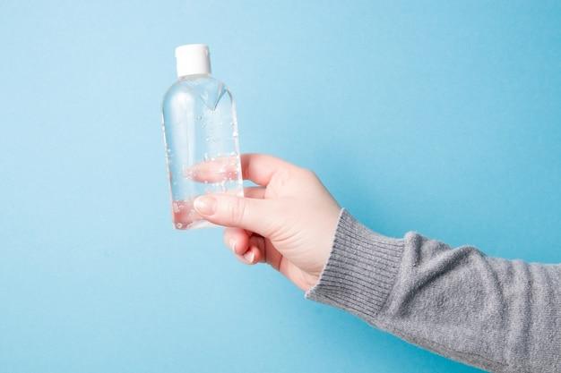 Mão feminina segura um gel desinfetante em uma pequena garrafa de plástico transparente com uma tampa branca em uma superfície escura