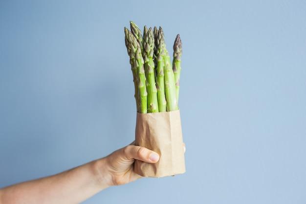 Mão feminina segura um pacote de espargos verdes no conceito de fundo azul de vegetarianos veganos e