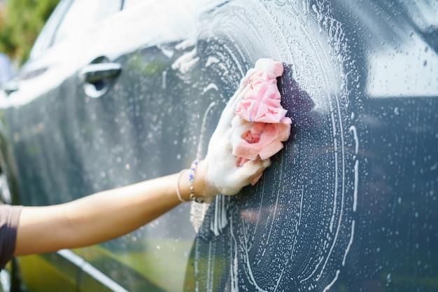 Mão feminina segura um pano de microfibra para lavar o carro. desinfecção de conceito e limpeza anti-séptica