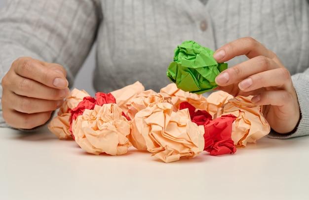 Mão feminina segura uma bola de papel verde amassado. nova ideia, brainstorming