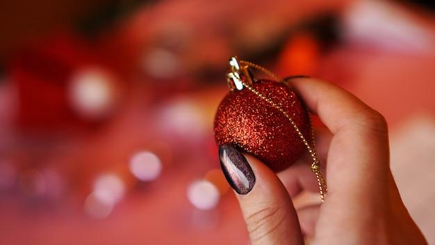 Mão feminina segura uma bola vermelha no fundo de natal decorado - luzes de bokeh
