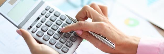 Mão feminina segura uma calculadora e uma caneta.