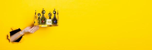 Mão feminina segura uma coroa de ouro em um fundo amarelo brilhante
