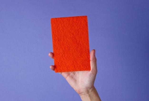 Mão feminina segura uma esponja abrasiva vermelha para se lavar em roxo