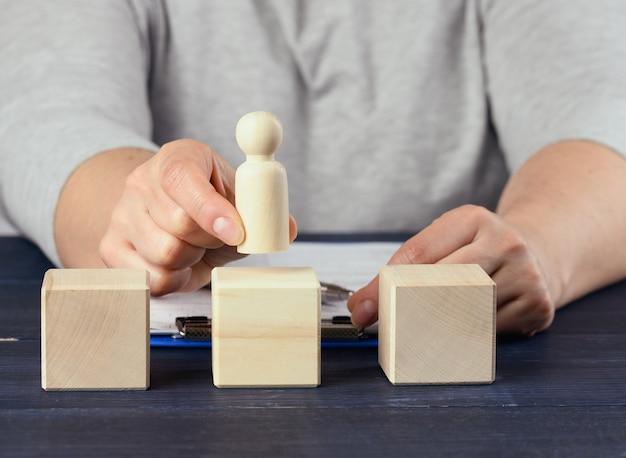 Mão feminina segura uma estatueta de madeira de um homem e coloca um cubo. conceito de promoção, coaching e mentoring