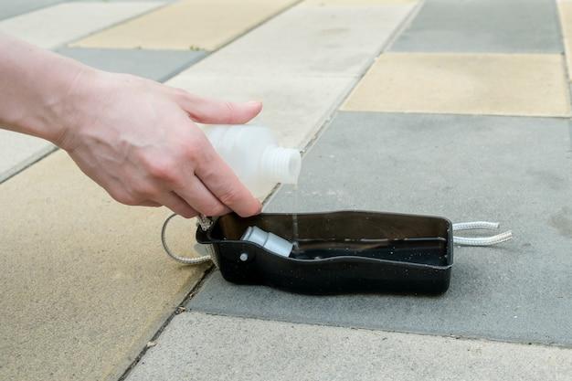 Mão feminina segura uma garrafa de água portátil para animais de estimação e derrama a água em um dispensador portátil para cães