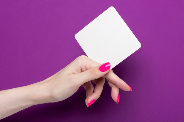 Mão feminina segura uma montanha-russa de um quadrado sobre um fundo roxo.