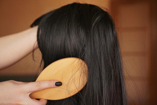 Mão feminina segura uma peruca preta com cabelo comprido e penteia um pente de madeira. cabeleireiro e cuidados com os cabelos