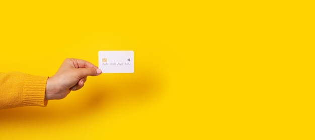 Mão feminina segurando a maquete de cartão de crédito branco em branco, cartão com chip eletrônico sobre fundo amarelo