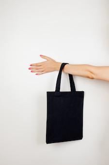 Mão feminina segurando a maquete de ecobag de algodão de uma pequena ecobag reutilizável preta feita de materiais reciclados ...