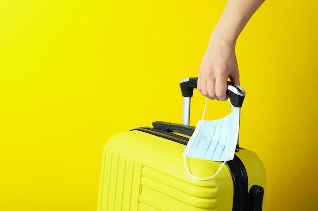 Mão feminina segurando bolsa de viagem e máscara médica em fundo amarelo