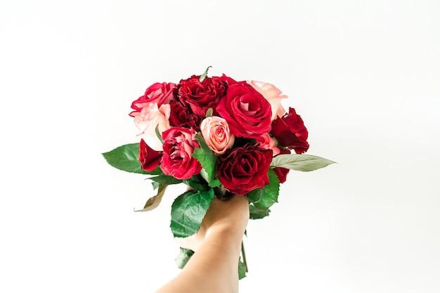 Mão feminina segurando buquê de flores rosa e rosa vermelha isolado no branco