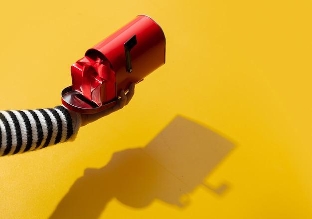 Mão feminina segurando caixa gfit na caixa de correio na superfície amarela
