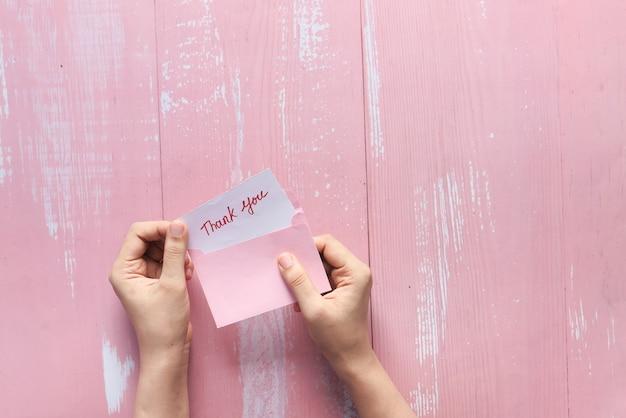 Mão feminina segurando carta de agradecimento, de cima para baixo