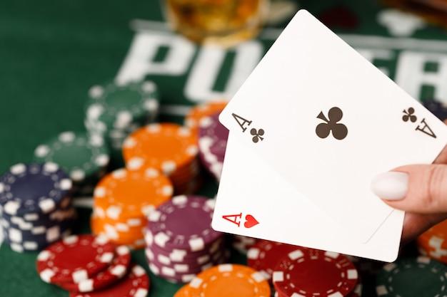 Mão feminina segurando cartas de jogar no cassino