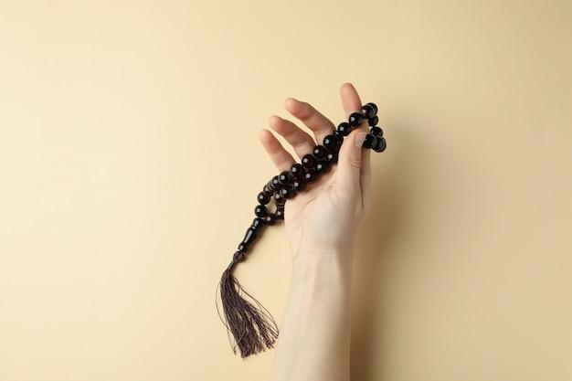 Mão feminina segurando contas de oração em superfície bege