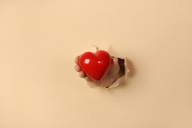 Mão feminina segurando coração vermelho pelo buraco de papel bege