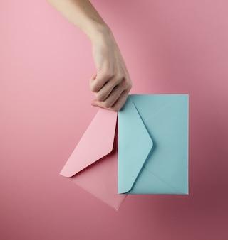 Mão feminina segurando dois envelopes em um fundo rosa pastel