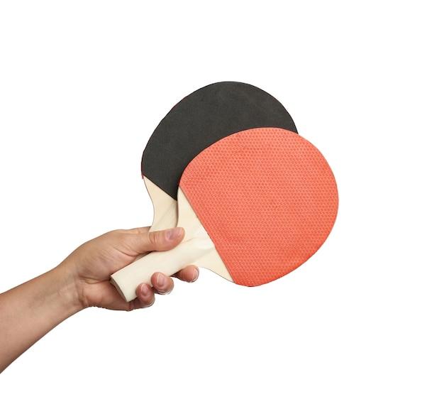 Mão feminina segurando duas raquetes de tênis de mesa de madeira