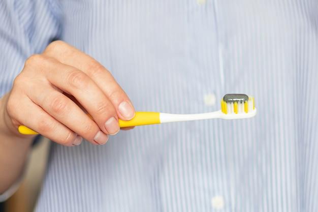 Mão feminina segurando escova de dentes amarela com pasta de dentes cinza final. conceito de odontologia. limpeza dos dentes. cuidados de saúde.
