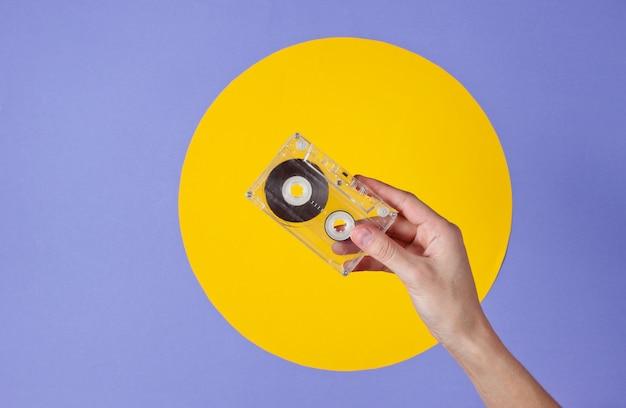 Mão feminina segurando fita cassete em roxo com círculo amarelo