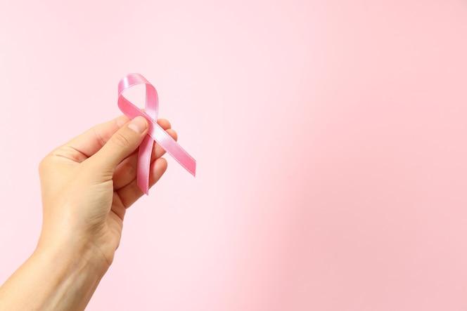 Mão feminina segurando fita de conscientização do câncer de mama em fundo rosa