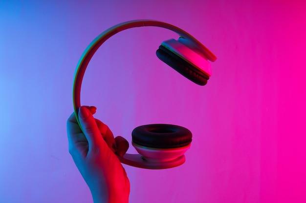 Mão feminina segurando fones de ouvido estéreo sem fio com luz gradiente neon azul-rosa