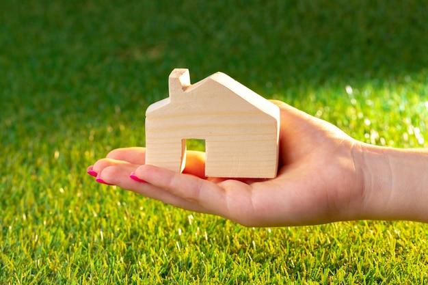 Mão feminina segurando modelo de casa de madeira acima da grama close-up