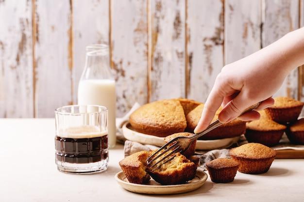 Mão feminina segurando muffins caseiros servidos com café em fundo de textura branco