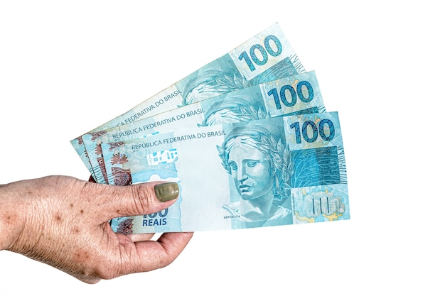 Mão feminina segurando notas de 100 reais, conceito de aposentadoria ou ajuda governamental Foto Premium
