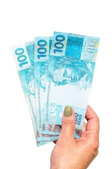 Mão feminina segurando notas de 100 reais, conceito de aposentadoria ou ajuda governamental