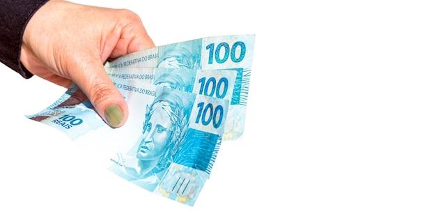 Mão feminina segurando notas de cem dólares em superfície branca isolada