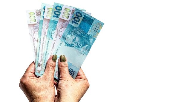 Mão feminina segurando notas de cento e duzentos reais em superfície branca isolada, conceito de pagamento ou benefício do governo