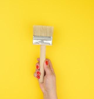 Mão feminina segurando novo pincel com cabo de madeira em um fundo amarelo, close-up