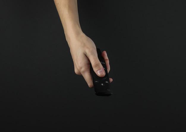 Mão feminina segurando o controle remoto da tv em fundo preto