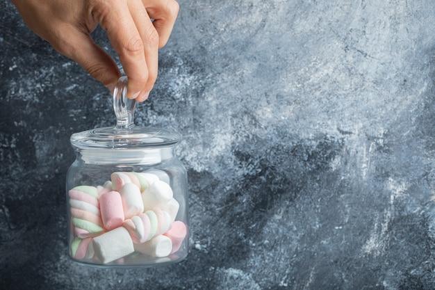 Mão feminina segurando o frasco de vidro de marshmallows coloridos no fundo de mármore