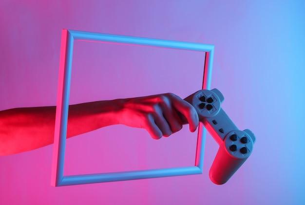 Mão feminina segurando o gamepad retrô em uma moldura elevada com luz holográfica de néon