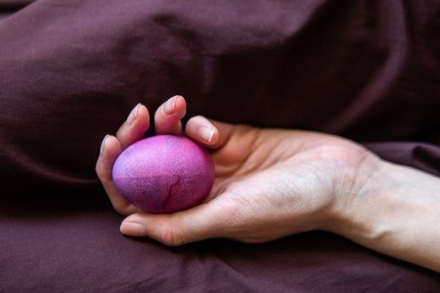 Mão feminina segurando o ovo de páscoa colorido. ovo brilhante festivo colorido pintou abstrata a colocação roxa na palma das meninas.