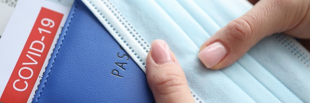 Mão feminina segurando o passaporte de vacinação cobiçoso e close das passagens de avião