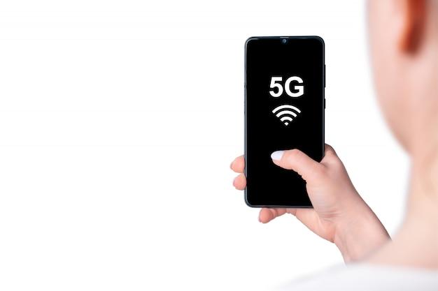 Mão feminina segurando o telefone celular com tela em branco 5g, maquete