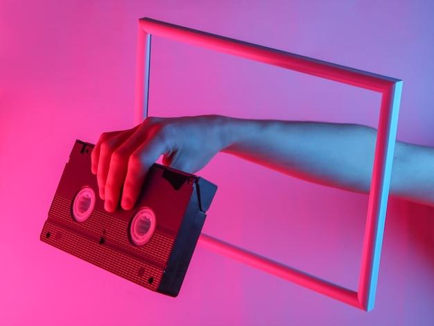 Mão feminina segurando o videocassete através de uma moldura elevada com luz holográfica de néon