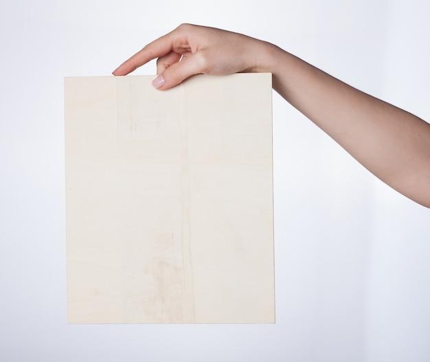 Mão feminina segurando outdoor em branco