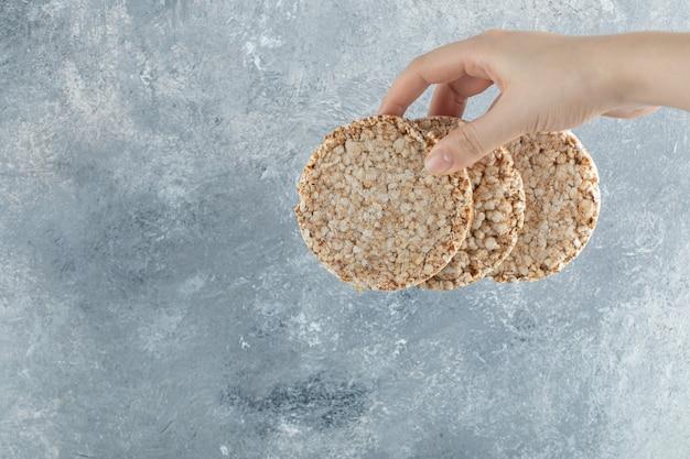 Mão feminina segurando pão crocante arejado na superfície de mármore