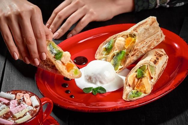 Mão feminina segurando pão doce de frutas em lavash servido com sorvete