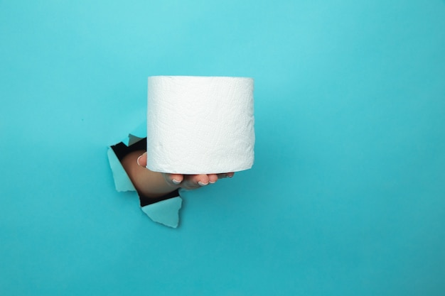 Mão feminina segurando papel higiênico através do fundo de papel azul rasgado