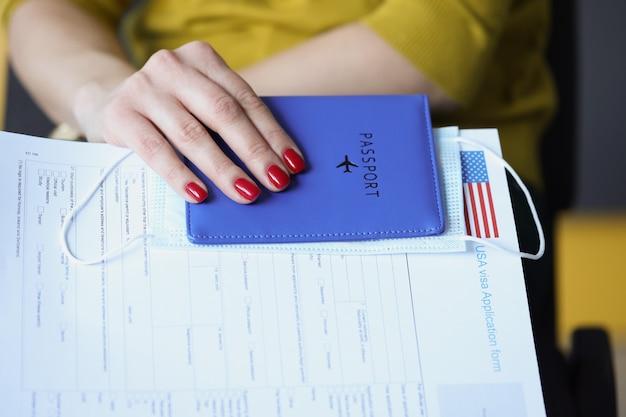 Mão feminina segurando passaporte com máscara protetora médica e documento para obter