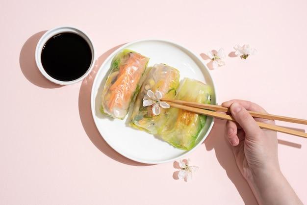 Mão feminina segurando pauzinhos e prato com rolinhos primavera e molho de soja