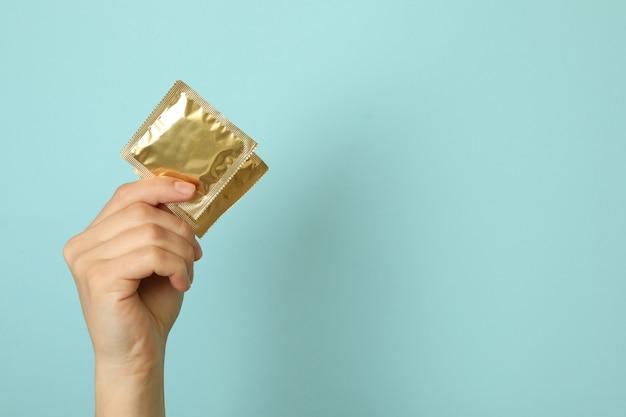Mão feminina segurando preservativos na parede azul, espaço para texto