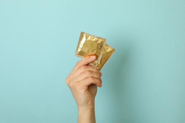 Mão feminina segurando preservativos na superfície azul