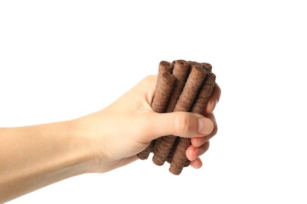 Mão feminina segurando rolos de wafer de chocolate, isolado no branco